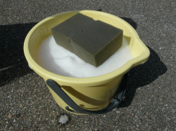 洗車用のバケツに濃縮原液カーシャンプー『パーフェクトシャンプー』を適量入れ、水を勢いよく注いで希釈したっぷり泡立たせます