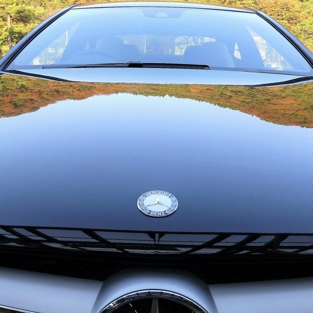 艶やかで美しい鏡面感で周囲の景色を映し出しているメルセデスベンツ・Cクラスクーペのボンネット(ボディカラーはブラック)